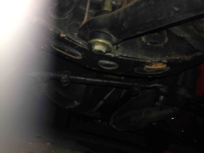 Here's the general area under the passenger side lower control arm. Notice the lower control arm is braced with a piece of sheet metal from FirmFeel. This stiffener plate is recommended for heavy duty front sway bars to reduce the stock lower control arms from twisting into mush with hot cornering.